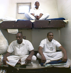 Photo: inmates seated in meditation on bunks