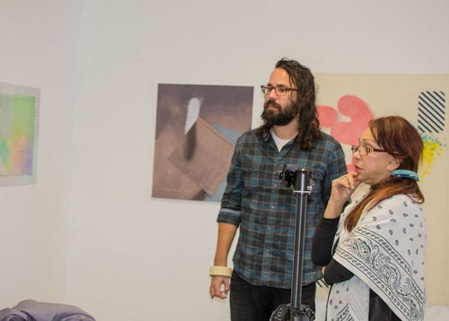 Photo: a bearded man and mature woman critique a painting